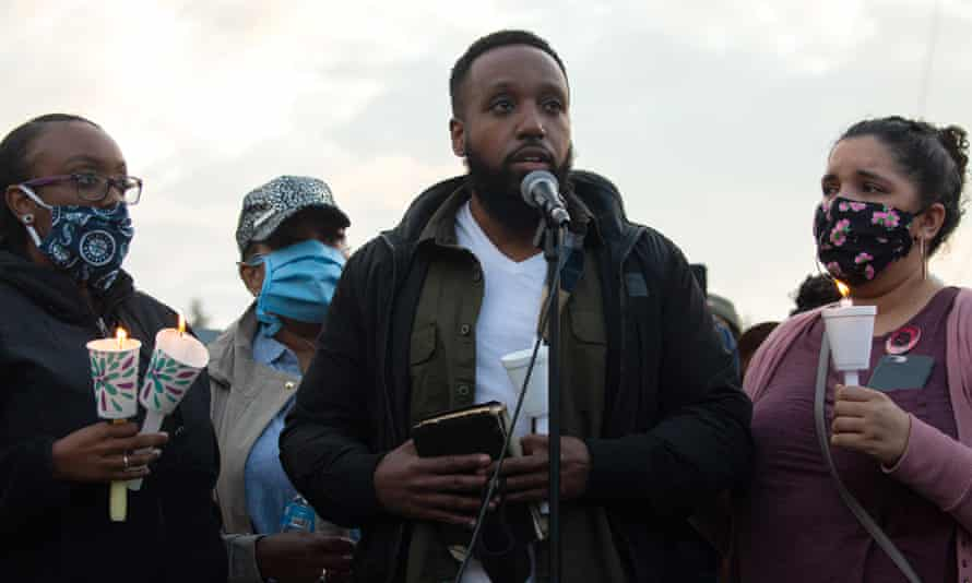 Matthew Ellis speaks while holding a Bible during a vigil for his brother, Manuel Ellis, on Wednesday.