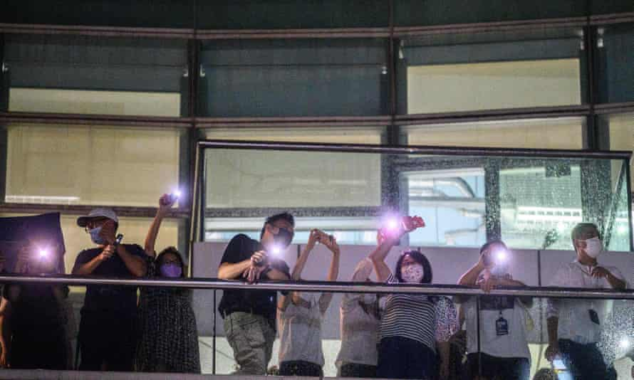 Apple Daily employees shine their phone torches in response to supporters below as the last edition went to press on 23 June.