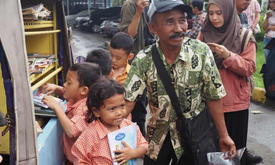 Sutino 'Kinong' Hadi helps children pick out books from his mobile library.