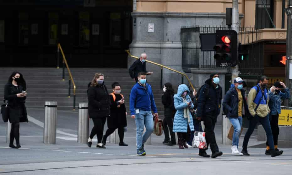 People wearing face masks cross the road outside Flinders Street station
