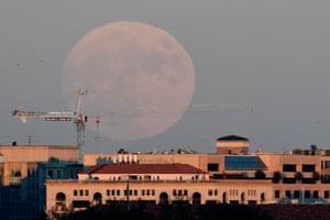 The moon rises over downtown Washington DC