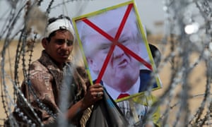 A demonstrator at the Israel-Gaza border in southern Gaza holds a poster of Donald Trump emblazoned with a red cross