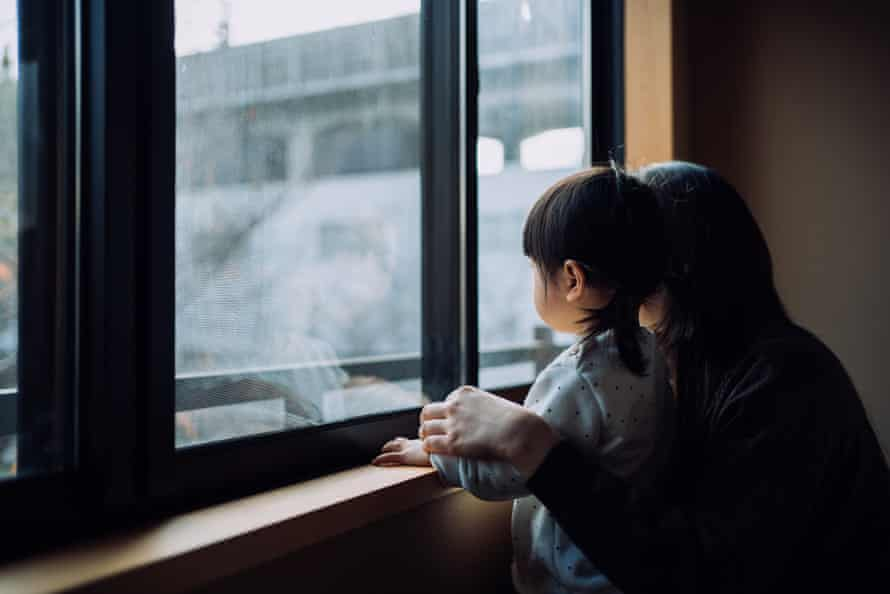 Young Asian mother and little daughter looking through window