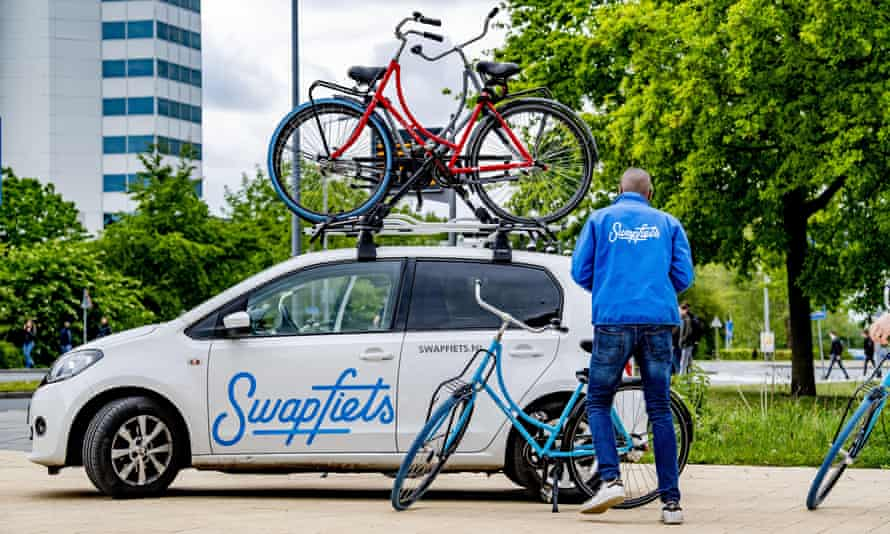 A Swapfiets employee with delivery car in Rotterdam