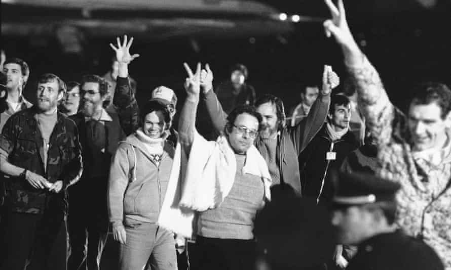Unidentified American hostages give the victory sign as they emerge from an Algerian aircraft in Algiers after their flight from Teheran where they had been held captive for 444 days in Iran, 21 January 1981.
