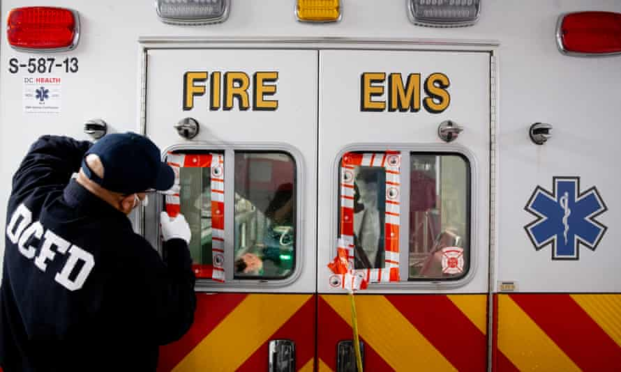 A firefighter seals the windows of an ambulance during the decontamination process after it was exposed to a suspected Covid-19 case in Washington DC.