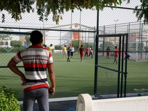 Migrant workers play football at the Challenger camp.