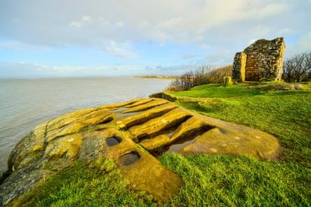'Stone coffins' and ruins of Saint Patrick's Chapel Heysham Head Lancashire. Morecambe Bay beyond