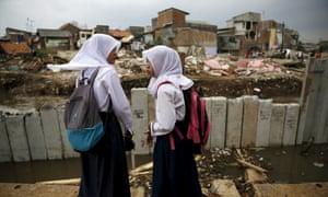 Schoolchildren stand near concrete floodwall