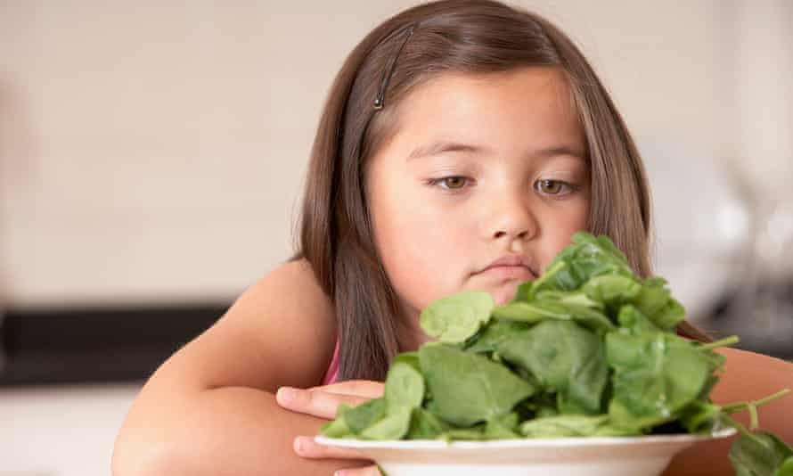 Young girl in kitchen with a bowl of spinach