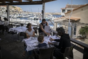 Diners apply hand sanitiser in Marseille