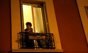 A woman looks from a window after gun shots were heard.