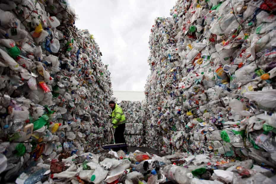 A worker sweeps stacks of plastic bottles at a recycling plant in Dagenham, Essex, UK.