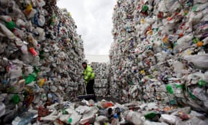An employee of the 'Closed Loop Recycling' plant sweeps stacks of plastic bottles at their plant in Dagenham on March 25, 2010 in London