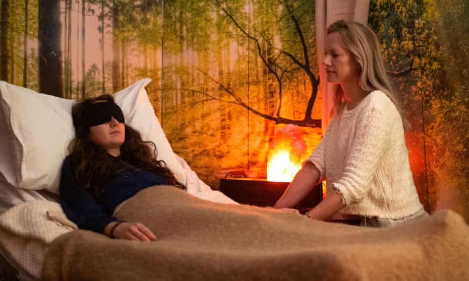 A woman lies on a bed, blindfolded, with a researcher monitoring her in The Psychedelic Drug Trial