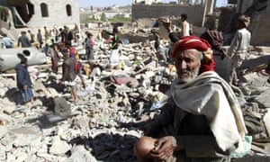 A Yemeni man sits on the rubble as people search for suvivors in houses destroyed by an overnight Saudi-led air strike on Sana'a.