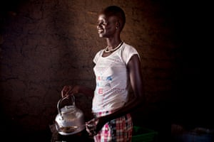 Helena, 16, poses with the kettle she uses for tea-making in her home in Rumbek, South Sudan