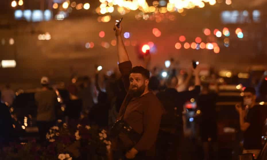 A man holding up a phone with a torch during a Minsk rally of opposition supporters, who accuse Lukashenko of falsifying the polls in the presidential election.
