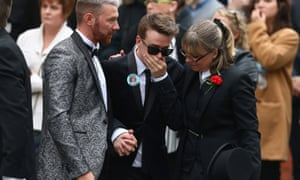 Martyn Hett's partner Russell Hayward in dark glasses, with his hand over his mouth, and being supported either side, at his funeral.