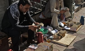 Afghan men count their money at a money market in Kabul