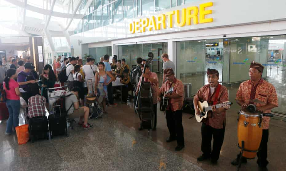 A group of musicians performs as they entertain passengers waiting for their delayed flights at Bali's Ngurah Rai International airport on Saturday.