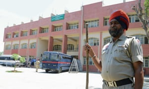 A policeman stands guard as a  bus arrives at court in Jammu and Kashmir