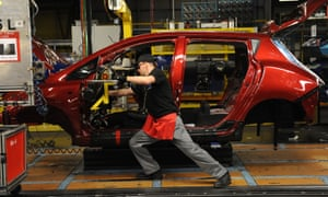 Factory worker adding dashboard to car.