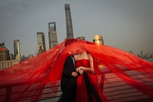 A couple pose on the Bund in front of the Shanghai Tower