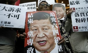 Pro-democracy activists hold up placards of Xi Jinping with slogans including 'End one party state' at a ferry terminal in Hong Kong.