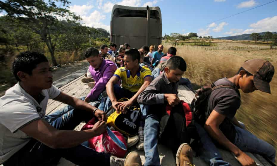 Hondurans, part of a new caravan of migrants travelling towards the US, ride in a trailer as they hitch a ride in Cucuyagua, Honduras, on Tuesday.