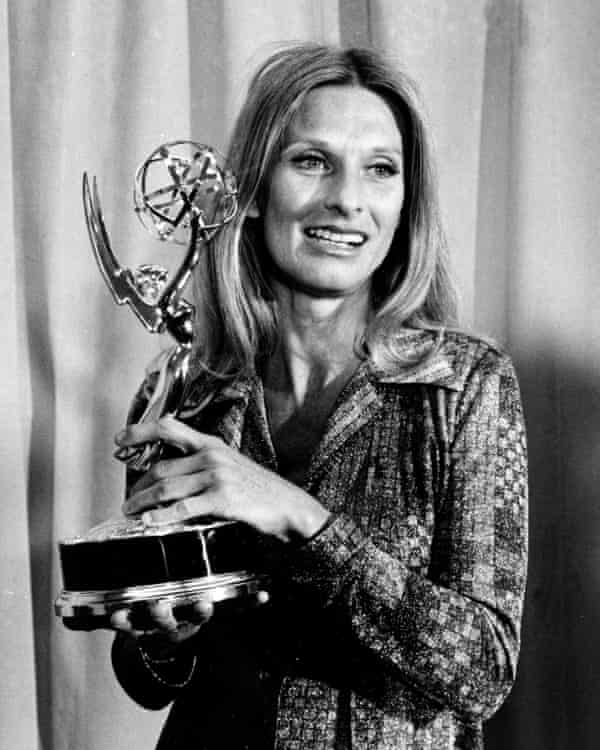 Black and white photograph of Cloris Leachman smiling while looking off camera and holding an Emmy award