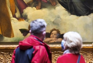 Visitors look at Raphael's Sistine Madonna at the Old Masters Gallery at the Zwinger palace complex in Dresden, Germany