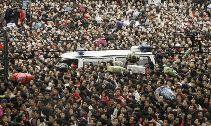 Thousands of passengers pack a main road as they wait to get into the Guangzhou Railway station.