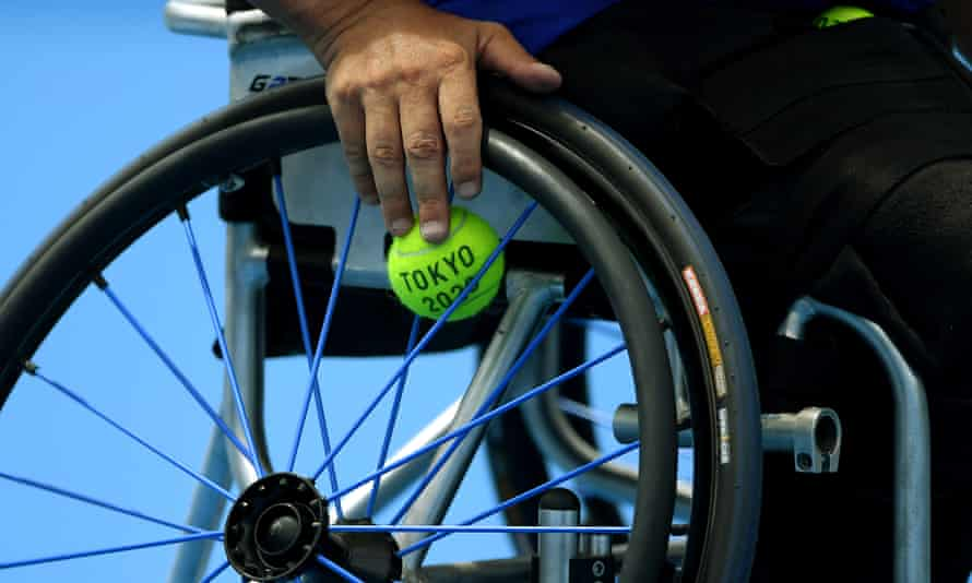 closeup of tennis ball in the spokes of a wheelchair