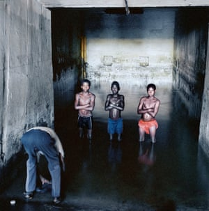 While Fernando Augusto Luta washes his clothes, Augusto Mokinda (13), Ze Jano (12) and Ze Ndala (10) stand in water that has risen from underground in an old mineshaft at Pomfret asbestos mine. The water probably contained blue asbestos fibres. 25 December 2002. From the series Asbestos (detail), 2002