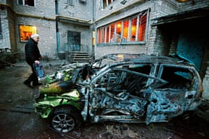 A man stands next to his car after it was destroyed by shelling today in the rebel-controlled city of Donetsk on Sunday.