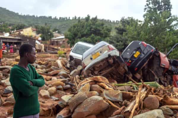 A man stands near the wreckage of vehicles washed away by Cyclone Idai in Chimanimani, eastern Zimbabwe, in March 2019