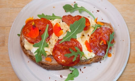 A round white plate with thick egg mayo, discs of chorizo and a few pieces of rocket on toast