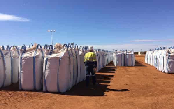 A Lynas Corp worker walks past sacks of rare earths waiting to be shipped to Malaysia in 2019.