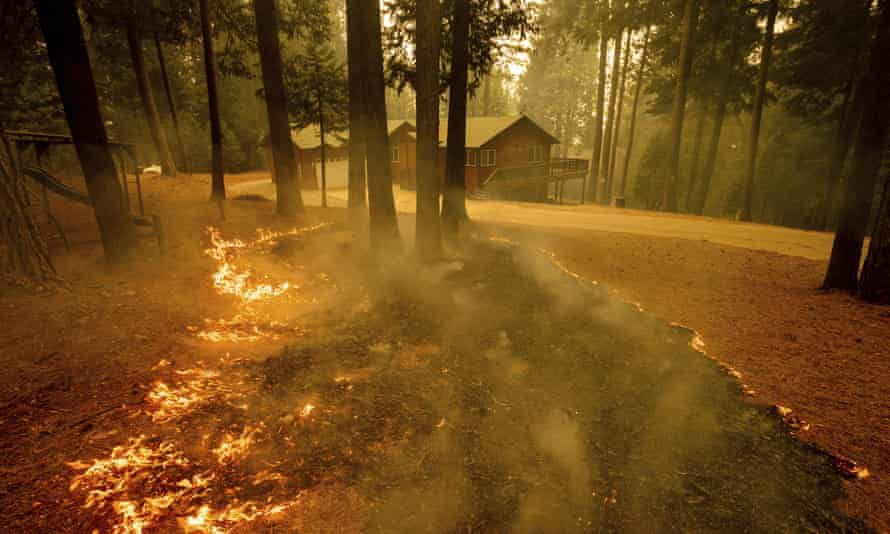 Flames from the Caldor Fire scorch the ground near a structure in Grizzly Flats, California, on Wednesday.