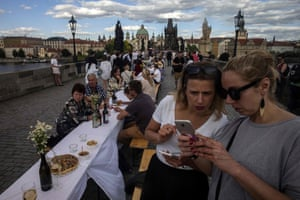 People sit at a half-kilometre long table set up on the Charles Bridge in Prague to celebrate the end of restrictions linked to coronavirus.