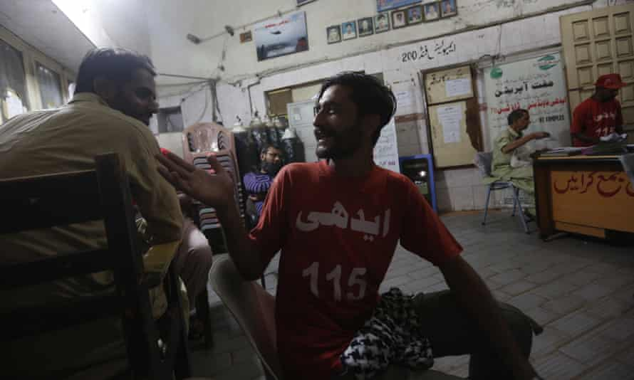 Safdar chats with his colleague at the Edhi Foundation office in Karachi.