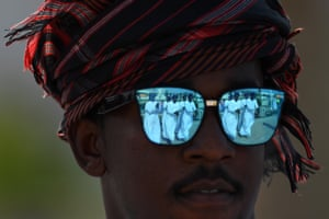 Dancers are reflected in a pair of sunglasses as crowds gather to watch the 10th Tour of Oman cycle race in Muscat
