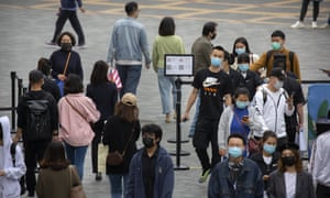 People wear face masks to protect against the spread of coronavirus as they walk through a temperature checkpoint at an outdoor shopping area in Beijing.