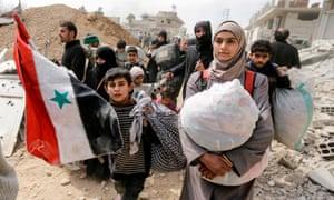 People walk through a regime-controlled corridor in Hawsh al-Ashaari, east of the Ghouta town of Hamouria.