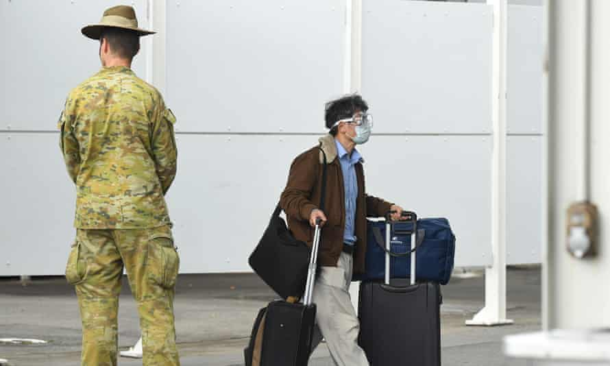 A member of the Defence Force watches over as returning overseas travellers are ushered towards waiting buses for the beginning of their 14-day quarantine after arriving at Sydney International Airport in Sydney, Australia, 29 March 2020.