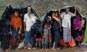 Rohingya refugees shelter from the rain in a camp in Cox's Bazar, Bangladesh, on Sunday