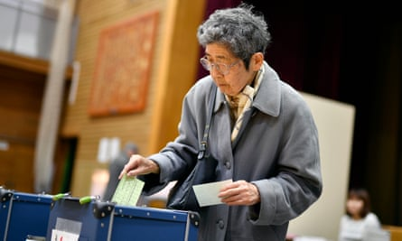 A woman casts her vote in Japan's general election. Shinzo Abe's ruling Liberal Democratic party is expected to win more than 300 of the 465 seats.