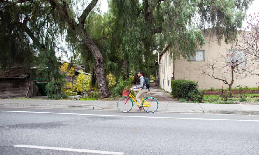 A Google employee bikes in front of the Martinellis' property at 1851 Charleston Road, in the middle of the Google campus.
