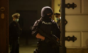 A police officer stands on guard in front of the Ministry of the Interior as a press conference follows talks about gunshots in Vienna.